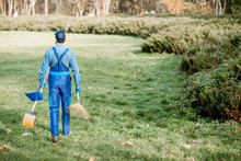 Professional Sweeper Or Gardener In Working Uniform Walking With Cleaning Tools In The Garden