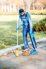 Professional Sweeper In Uniform Sweeping Leaves With Broom And Scoop On The Street