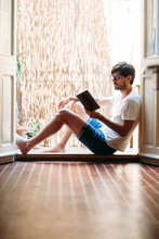 Young Man Reading Book Sitting On Balcony At Home