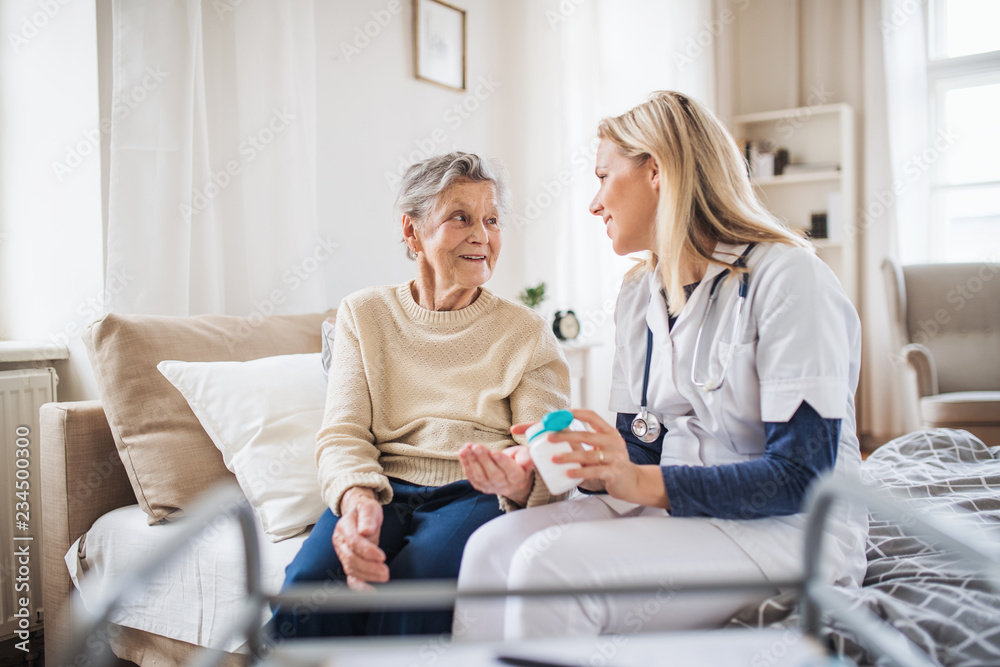 Fototapety, obrazy: A health visitor explaining a senior woman how to take pills.