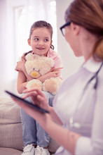 Cute Girl. Cute Little Dark-haired Girl Sitting With Her Toy Listening To Family Practitioner Attentively