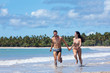 A young couple running along a tropical beach together and holding hands