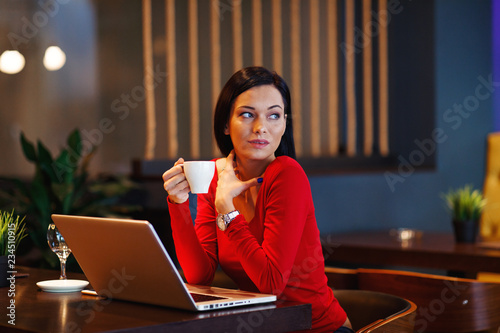 Fotografie, Obraz  Beautiful young woman holding coffee in a cafe with a laptop on the table