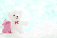 One White Teddy Bear With Red Bow And Pink Christmas Cap On Blur Blue And White Background Have Copy Space
