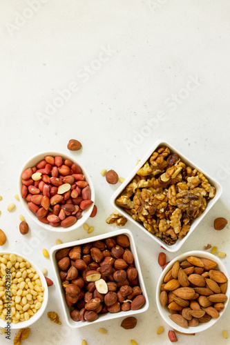 Various nuts in a ceramic bowl (walnut, almonds, pine nuts, hazelnuts) on a light stone table. The concept of a healthy dessert.Top view flat lay background. Copy space.