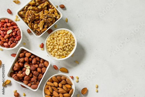 Various nuts in a ceramic bowl (walnut, almonds, pine nuts, hazelnuts) on a light stone table. The concept of a healthy dessert. Copy space.
