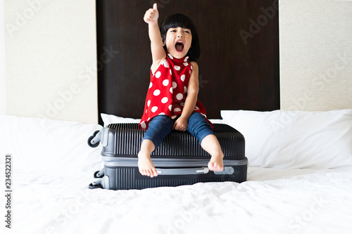 Fotografia  Happy Asian cute girl or kid is sitting on the baggage and ready to go to travel in aboard