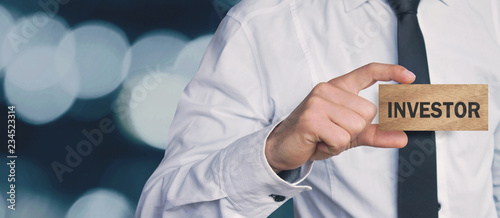Valokuva  Businessman showing Investor word in wooden block