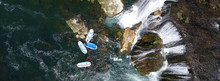 Group Of People Doing White Water Rafting Activity On Wild River With Waterfall