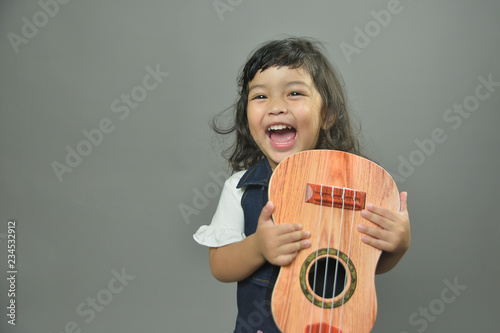 Asian little child girl holding  ukulele with smile isolated on gray background. Music,musician and guitarist concept  - 234532912