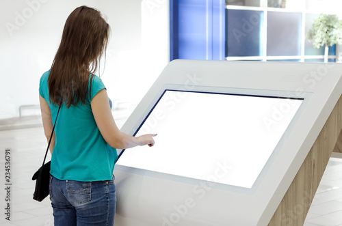 Vászonkép  Woman is using a blank touch screen of interactive information stand in the supermarket