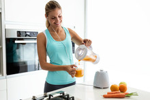 Beautiful Young Sporty Woman Serving Detox Orange Juice Into Glass While Listening Music In The Kitchen.