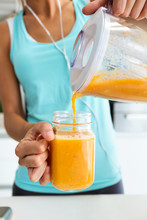 Hands Of Woman Serving Detox Orange Juice Into Glass In The Kitchen.