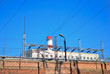 Old brick fence on a background of blue sky and electrical power station. Industrial tourism. High chimney pipe