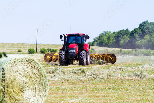 Red tractor with hay rake