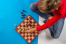 Kid Sitting Near Chessboard And Play Chess Game