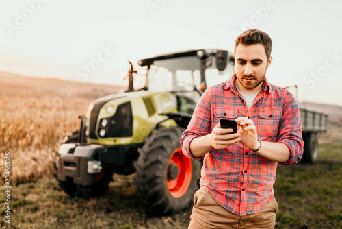 Farmer working and harvesting using smartphone in modern agriculture with tractor background