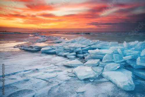 Foto op Plexiglas Kust Winter landscape on seashore during sunset. Lofoten islands, Norway. Ice and sunset sky. Natural winter landscape