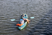 Man Fishing In A Kayak On A Peaceful Lake