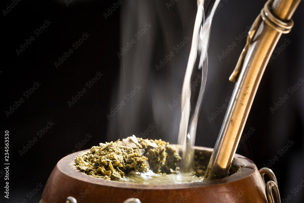 Fototapeta Water served into steaming yerba mate infusion