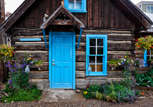 A Cute Log Cabin With A Bright Blue Door And Windows