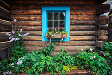 A Colorful Blue Window On A Log Cabin With A Garden Of Flowers