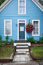 A Colorful Blue House With Hanging Flowers And Blue Door