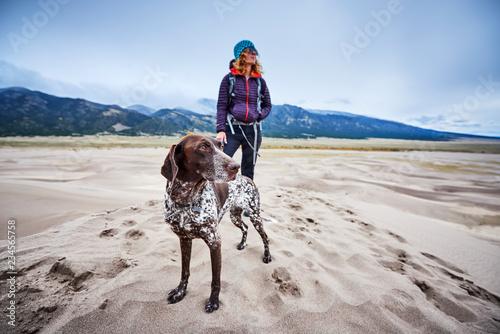 Obraz na płótnie a young woman and her dog hiking among sand dunes