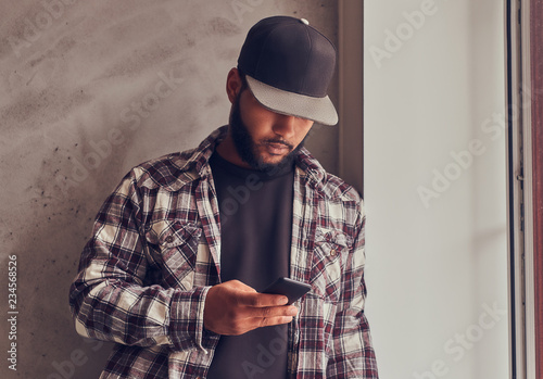 Valokuva  African-American bearded man chatting in the social network while standing next gray textured wall