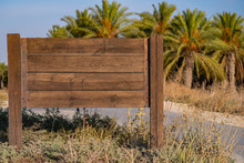 Blank Wooden Road Sign On Palm Plantation Background