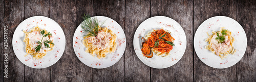 Set of pasta from worldwide cuisines. Fettuccine pasta meat, seafood pasta with shrimp, oysters, octopus, cheese and herbs, in bowl on rustic wooden background. Top view. Italian cuisine. Top view