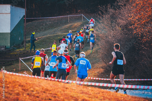 Group of professional cross country athletes running in competition in autumn nature. Sport or orienteering run concept