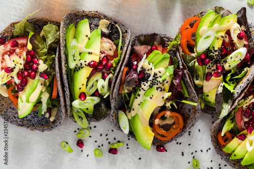 Fotografie, Tablou Gluten-free vegan tacos from black bean  with tomato and avocado salad  with tahini sauce and pomegranate seeds