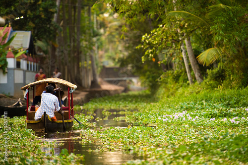 Some tourists are on a canoe sailing on the lush and green backwaters in Alleppey during the sunset, Kerala, India Canvas Print