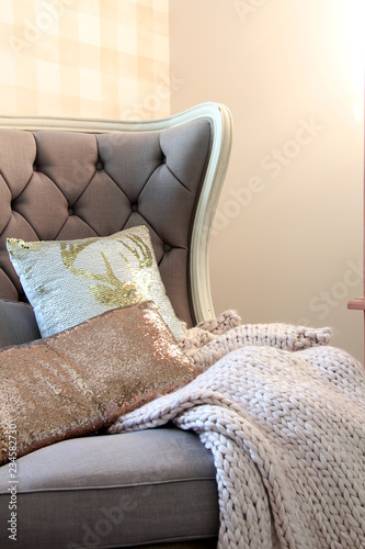 Cozy accent chair with chunky knit blanket in a bedroom with plaid wallpaper Canvas Print