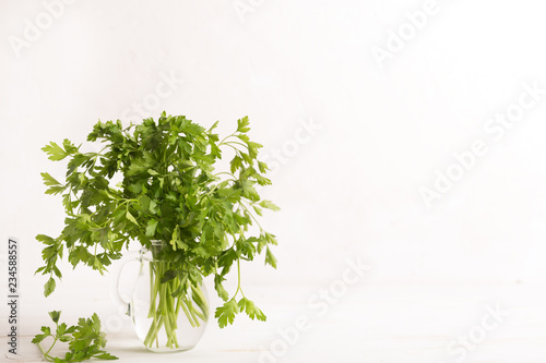 Fresh parsley leaves from the garden in the glass. White background