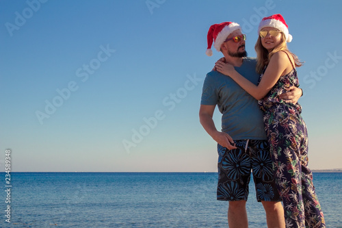 f912c3f6 smiling couple in christmas hats and sunglasses at the beach of the sea