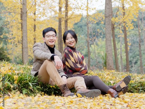 Photo  Asian couple in love sits on fallen leaves in park