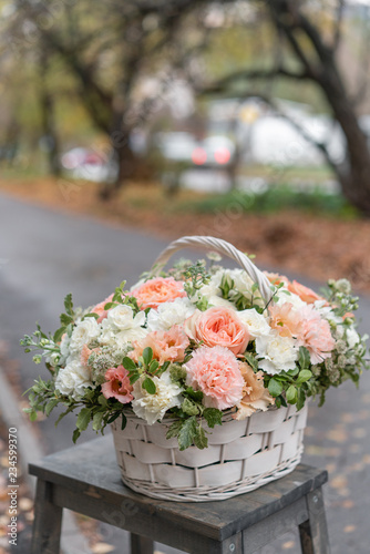 Foto op Canvas Bloemen Wicker basket with mix beautiful flowers on wooden table near gray wall. Beautiful garden flowers in the arrangement , the work of a professional florist. European floral shop