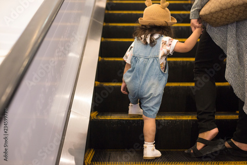 Fotografía Little Asian girl use escalators with her mother in the shopping mall, Kid is prohibited to use the escalator alone because it is very dangerous