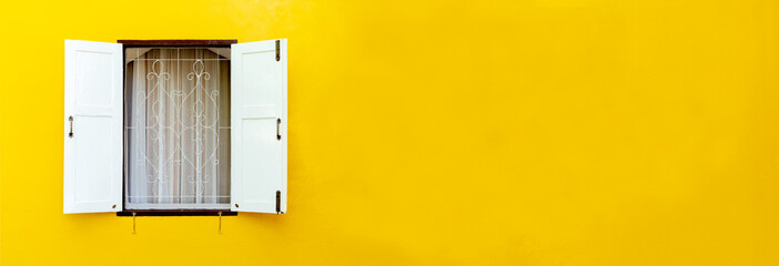 The white wooden window was opened, where the windows were on the concrete walls of yellow. with blank copy space.