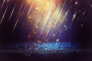 glitter vintage lights background. black, blue and gold. de-focused.