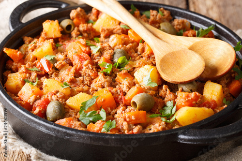 picadillo is a traditional dish made with ground beef, potatoes, onions, garlic, cumin, carrots, white wine, tomato sauce, raisins, olives and capers closeup. horizontal