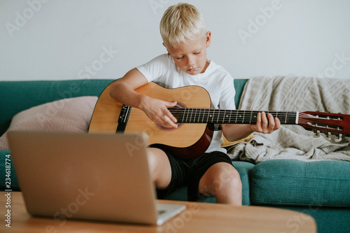 Boy learning to play guitar through a video call with his teacher