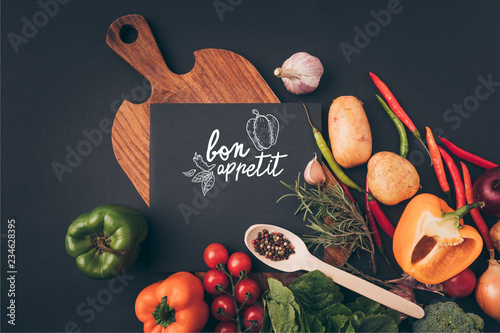 Plakaty do jadalni top-view-of-black-board-on-wooden-table-with-vegetables-on-gray-table-bon-appetit-lettering