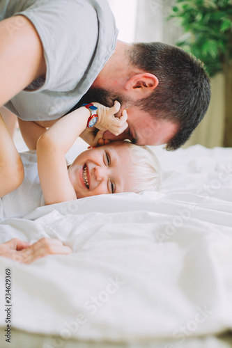 Fotografie, Obraz  father kissing his litle son on the bed with white linen