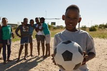 Boy Holding Football In The Ground