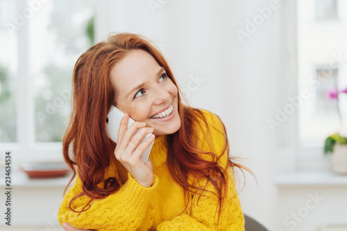 Cuadros en Lienzo Cheerful red-haired woman talking on phone