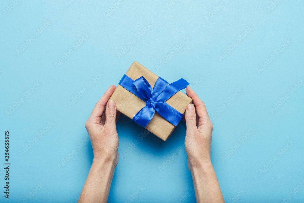 Fototapety, obrazy: Female hands holding a gift with a blue ribbon on a blue background. Concept of a gift for the holidays, birthday, Christmas, wedding. Flat lay, top view