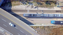 Modern Passenger Train Leaving A Train Station - Aerial Footage